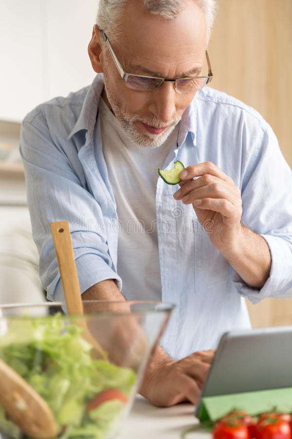 Handsome concentrated mature man cooking salad using tablet royalty free stock images