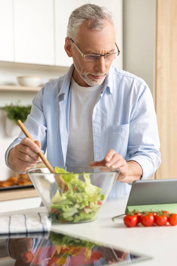Handsome concentrated mature man cooking salad using tablet stock photo
