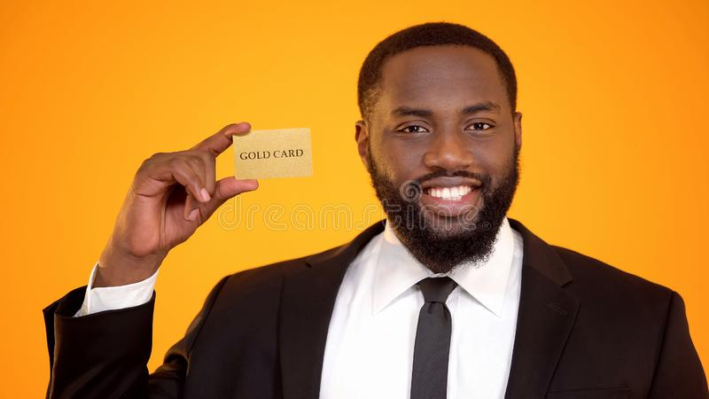 Handsome confident african-american man in suit presenting gold card, member. Stock photo royalty free stock photography