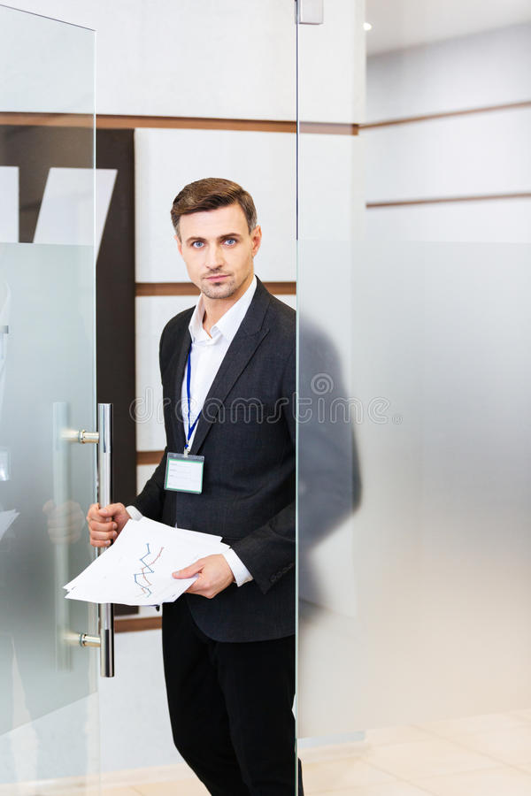 Handsome confident businessman entering the office. Handsome confident businessman in black suit entering the office royalty free stock image