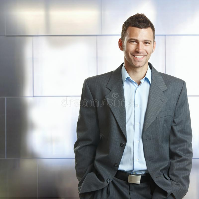 Handsome confident businessman hands in pocket. Handsome happy confident caucasian businessman hands in pocket, suit with no tie. Smiling, standing, looking at royalty free stock images