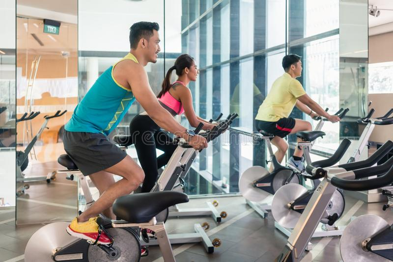 Handsome and confident young man during group class of HIIT indoor cycling stock photos