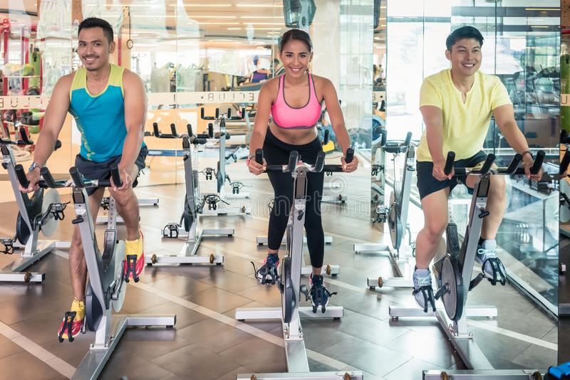 Handsome and confident young man during group class of HIIT indoor cycling royalty free stock photography