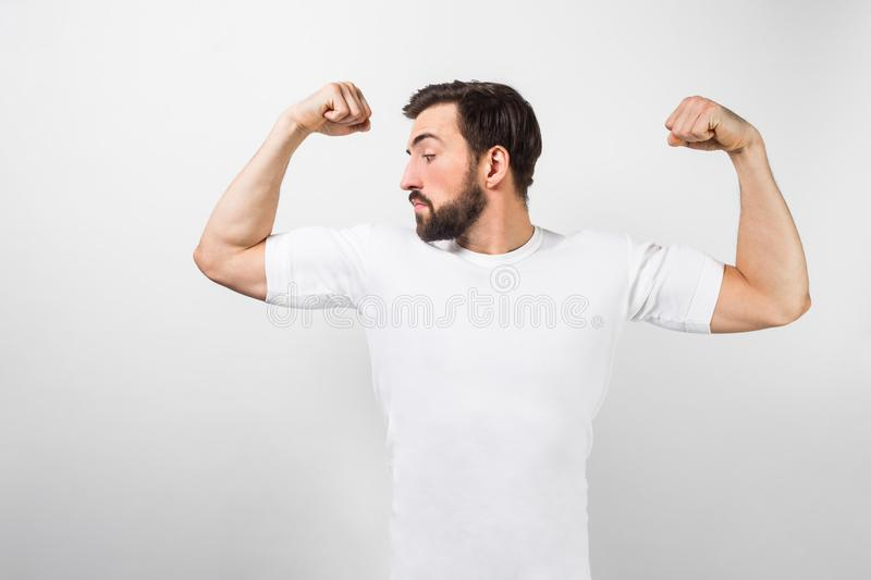 A handsome confident young man standing and showing big muscles on his hands. He is looking at one of them and very royalty free stock image