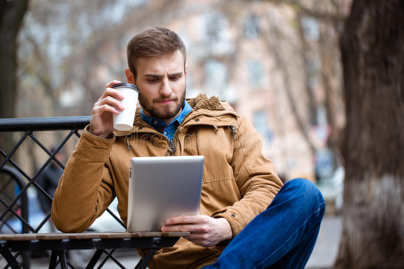 Handsome consentrated bearded man using tablet in open air cafe stock images
