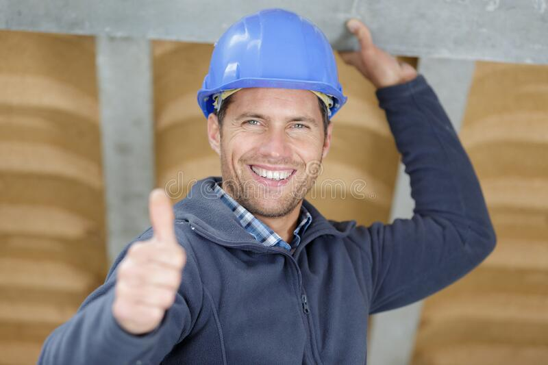 Handsome construction worker showing thumbs up stock photo