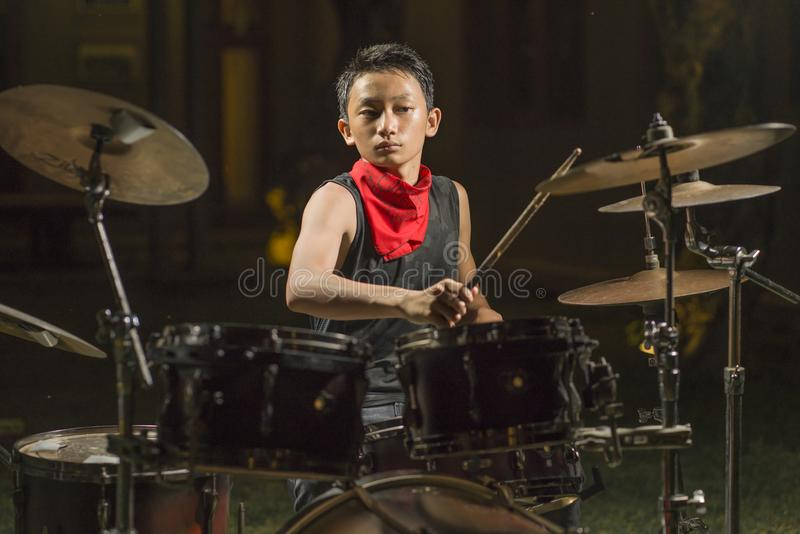 Handsome and cool Asian American teenager playing drum set at home garden emulating night music show as hobby in teenage  love royalty free stock image