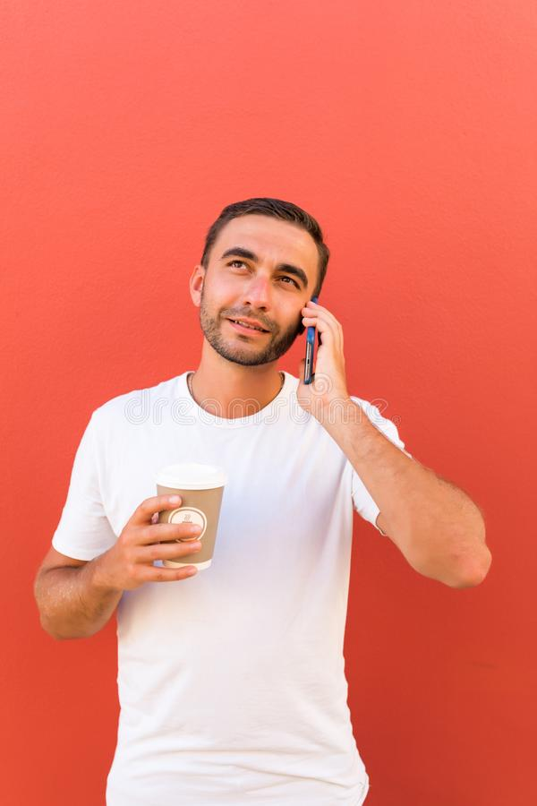 Handsome cool man with coffee cup to go talk on phone isolated on red background. Handsome cool man with coffee cup to go talk on phone on red background royalty free stock images