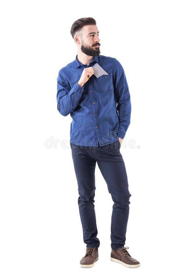 Handsome cool relaxed bearded guy put cellphone in shirt pocket looking away. Full body isolated on white background stock images