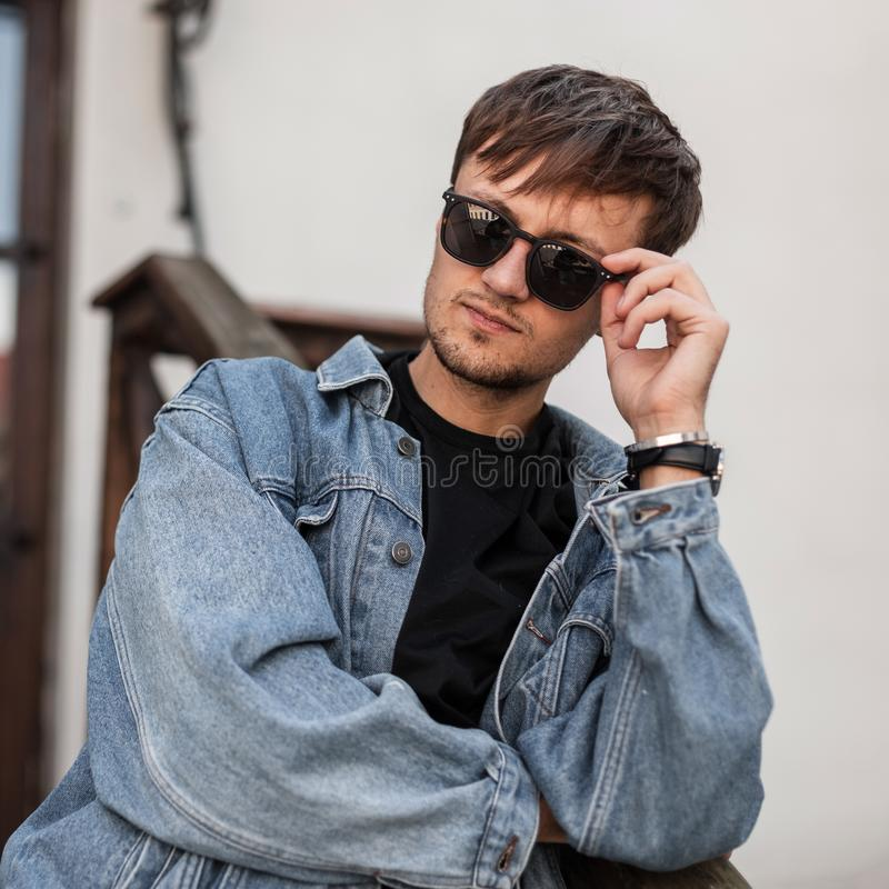 Handsome cool young man hipster straightens fashionable black sunglasses. Portrait of a handsome guy. In a stylish blue denim jacket in a black t-shirt outdoors stock images