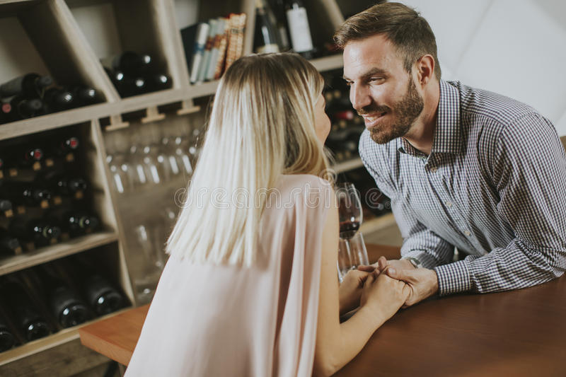 Handsome couple on the date sitting by table in wine bar. Handsome young couple on the date sitting by table in wine bar royalty free stock images