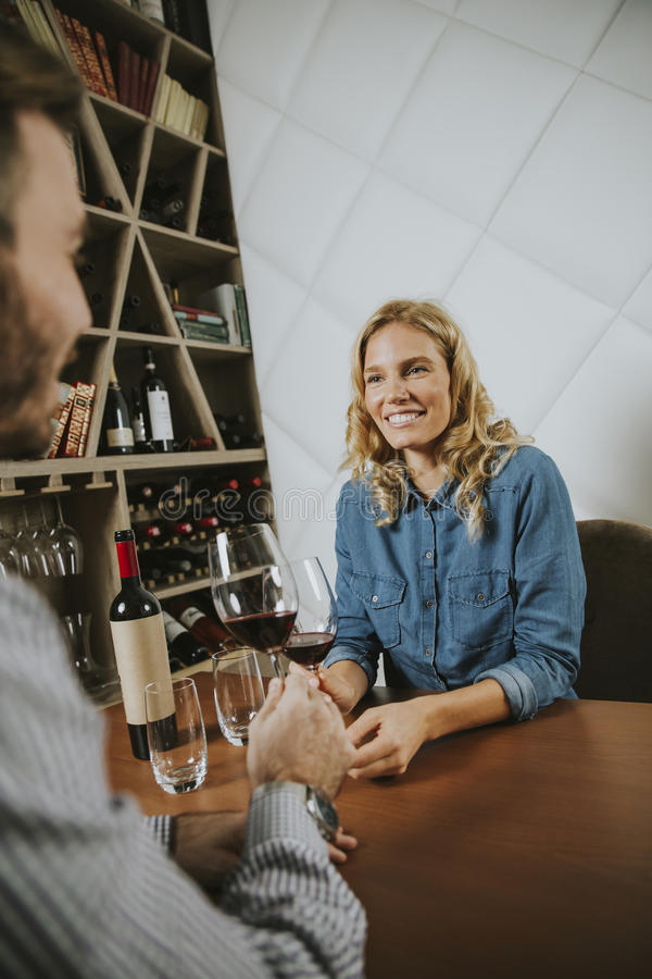 Handsome couple on the date sitting by table in wine bar. Handsome young couple on the date sitting by table in wine bar stock photography