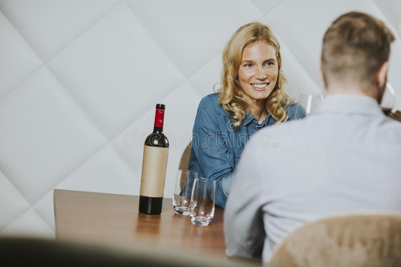 Handsome couple on the date sitting by table in wine bar. Handsome young couple on the date sitting by table in wine bar stock images