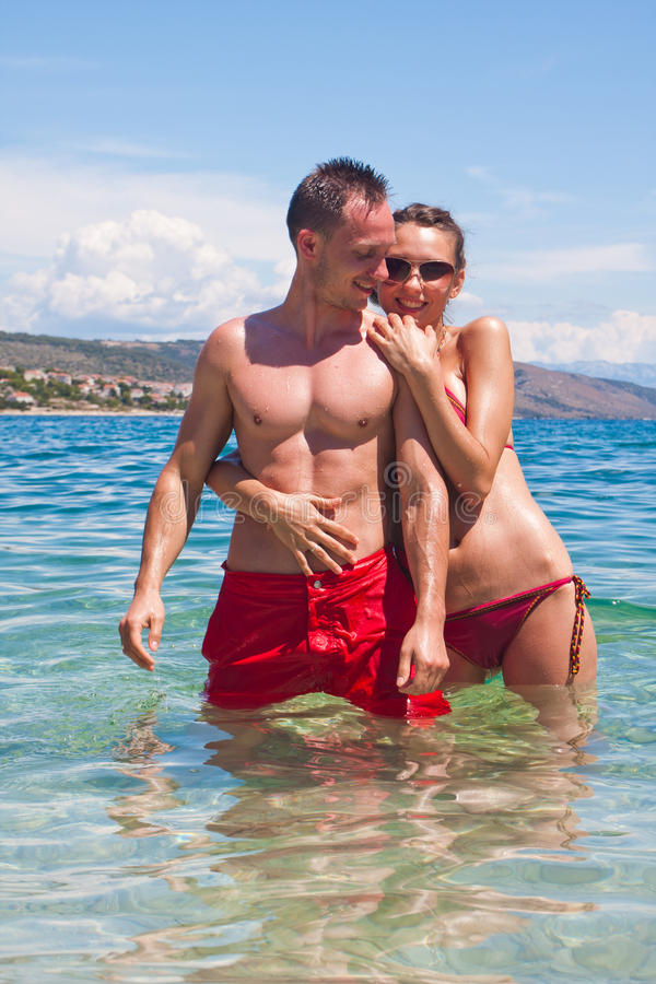 Handsome couple hugging in water stock image