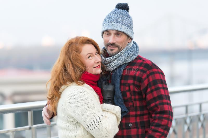 Handsome couple likes walking in city. Aged guy and woman likes winter. Rude woman cuddles to guy in red jacket. Man and woman. Handsome couple likes walking in stock image