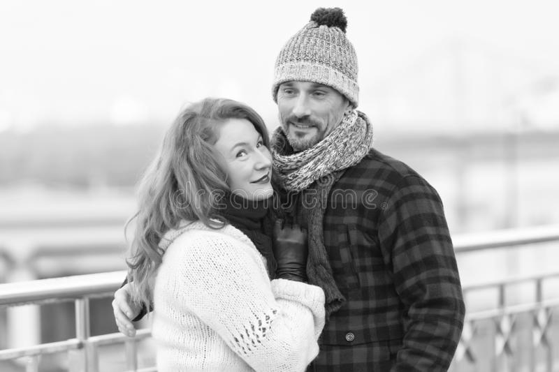 Handsome couple likes walking in winter city. Women cuddles to boyfriend in flannel jacket. Handsome couple likes walking in city. Aged guy and women likes royalty free stock images
