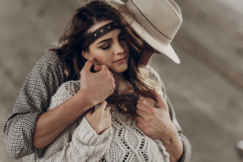 Handsome cowboy man in white hat touching cheek of beautiful boho gypsy woman with leather headband, face closeup portrait stock image