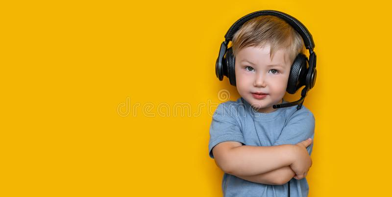 Handsome cute blonde little boy three years old in gaming black headphones. look at camera, grey eyes and grey t-shirt on yellow. Handsome cute blonde little boy royalty free stock images