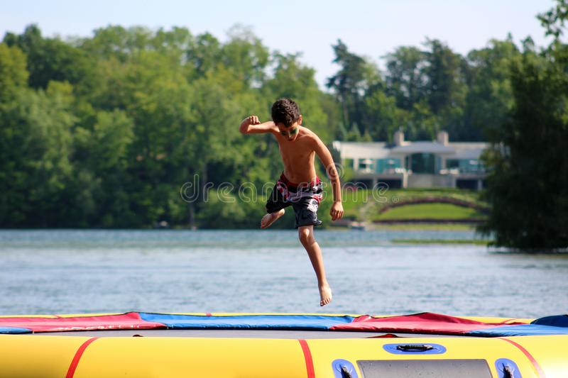 Handsome cute boy jumping at a water trampoline floating in a lake in Michigan during summer. royalty free stock image