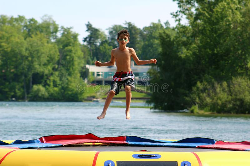 Handsome cute boy jumping at a water trampoline floating in a lake in Michigan during summer. stock photography