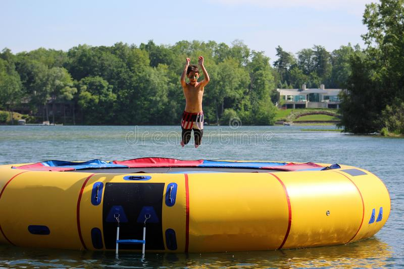 Handsome cute boy jumping at a water trampoline floating in a lake in Michigan during summer. royalty free stock images