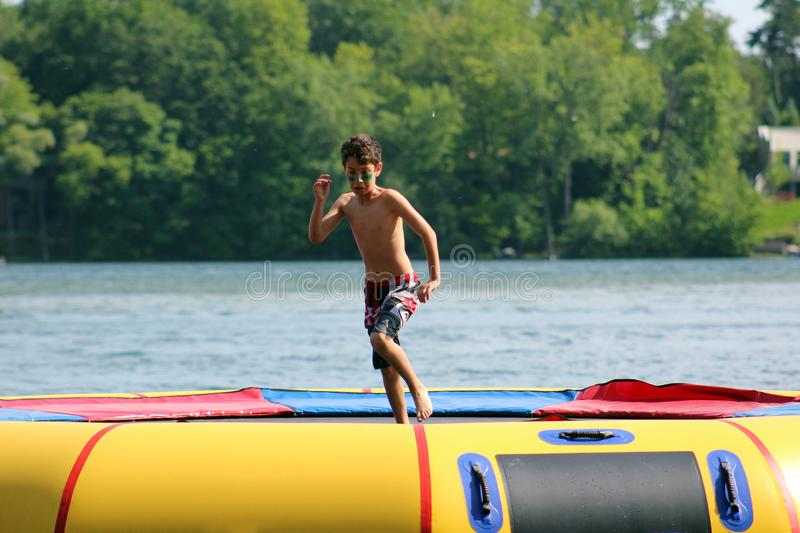 Handsome cute boy jumping at a water trampoline floating in a lake in Michigan during summer. stock photos