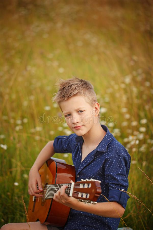 Handsome cute boy is playing on acoustic guitar in outdoor royalty free stock images