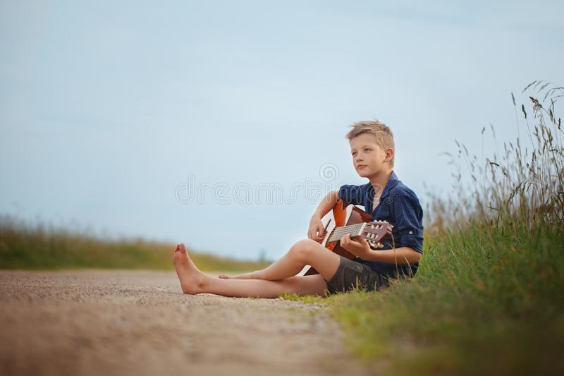 Handsome cute boy is playing on acoustic guitar sittingon road in summer day. stock photography