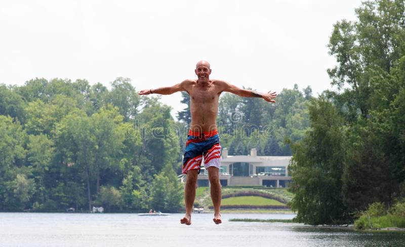 Handsome cute man jumping at a water trampoline floating in a lake in Michigan during summer. royalty free stock image