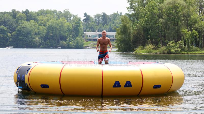 Handsome cute man jumping at a water trampoline floating in a lake in Michigan during summer. stock photo