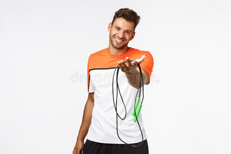 Handsome and cute smiling sportsman extend arm and suggest use his jumping rope, grinning. Charismatic fitness stock photo