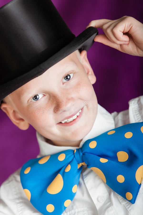 Handsome dapper little boy in a top hat. And enormous blue and yellow polka dot bow-tie doffing his hand to the brim with a lovely sweet smile, close up cropped royalty free stock image