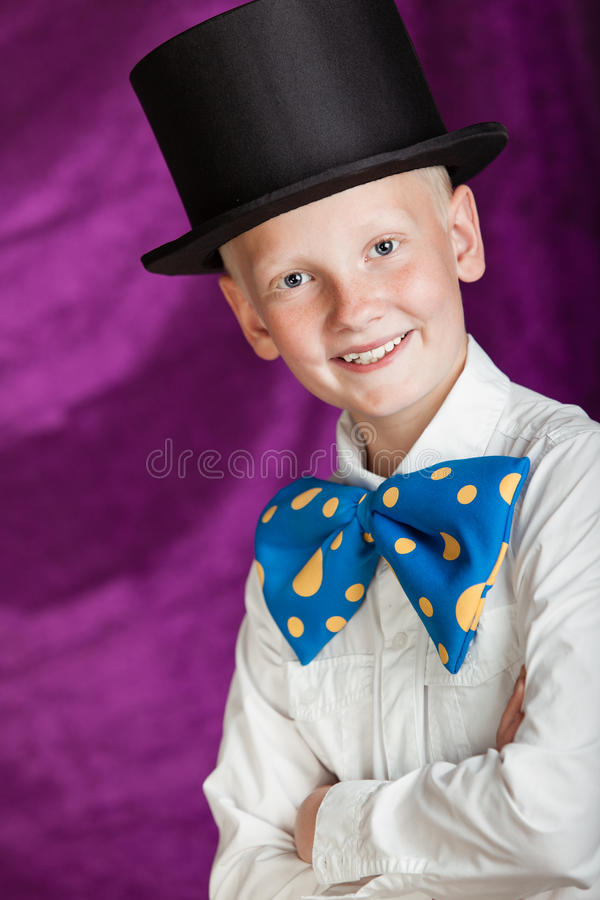 Handsome dapper young boy in a top hat. And huge colorful blue polka dot bow-tie grinning at the camera with folded arms, purple backdrop stock photo