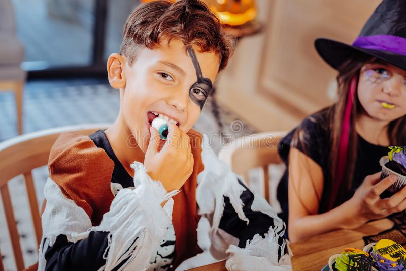 Handsome dark-eyed boy wearing pirate suit for Halloween eating gummy eye. Gummy eye. Handsome dark-eyed boy wearing pirate suit for Halloween feeling excited stock photos