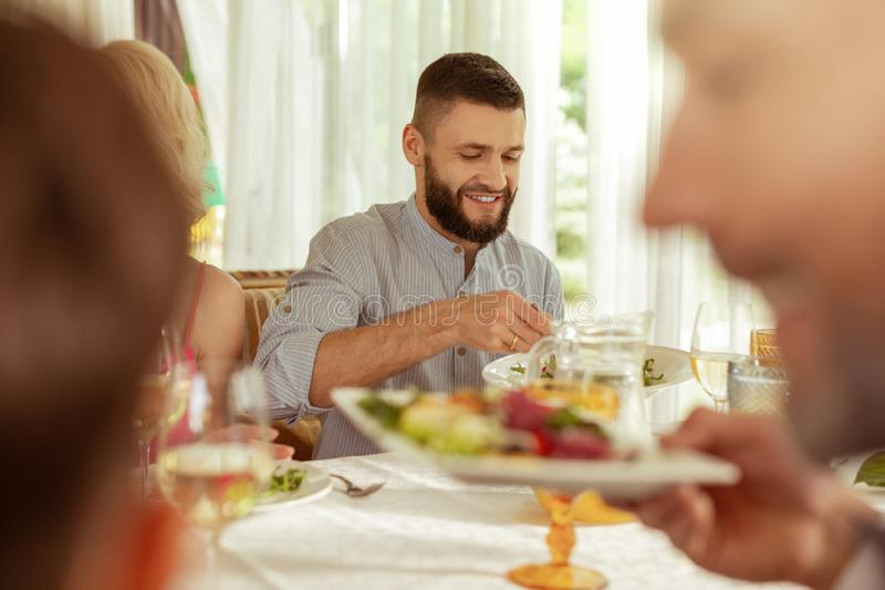 Handsome dark-haired man having lunch with parents royalty free stock photos