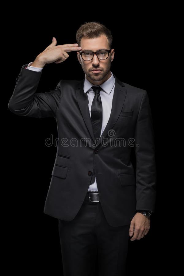 Handsome depressed businessman in black suit with hand gun sign stock image