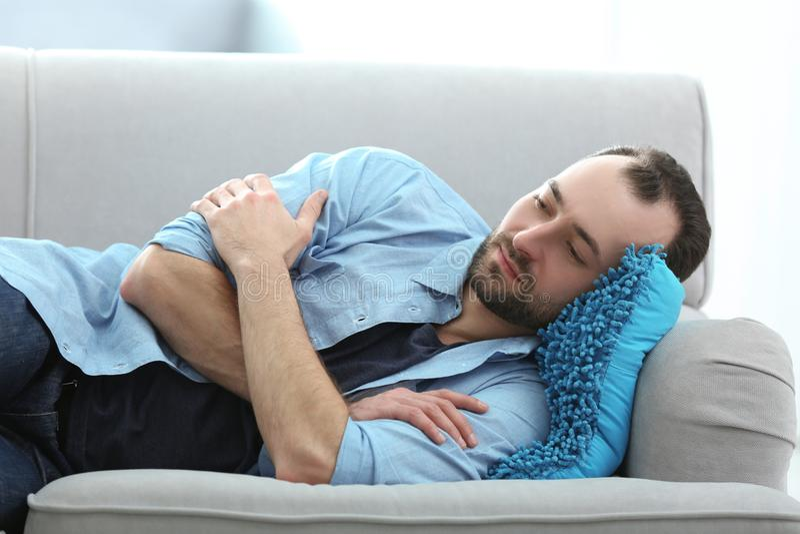 Handsome depressed man lying on sofa stock photo