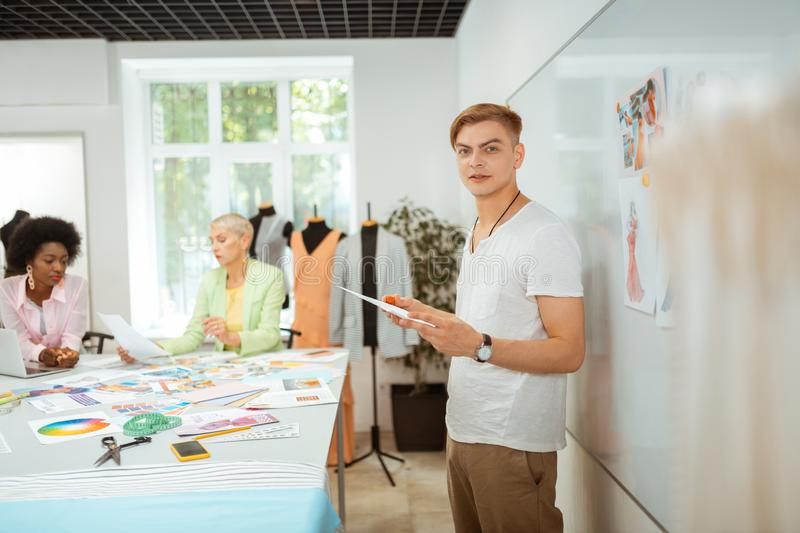 Handsome designer holding a sketch in his hand royalty free stock images