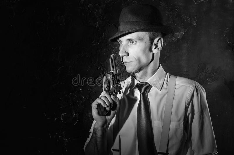 Handsome detective in hat holding a gun in the dark royalty free stock photos