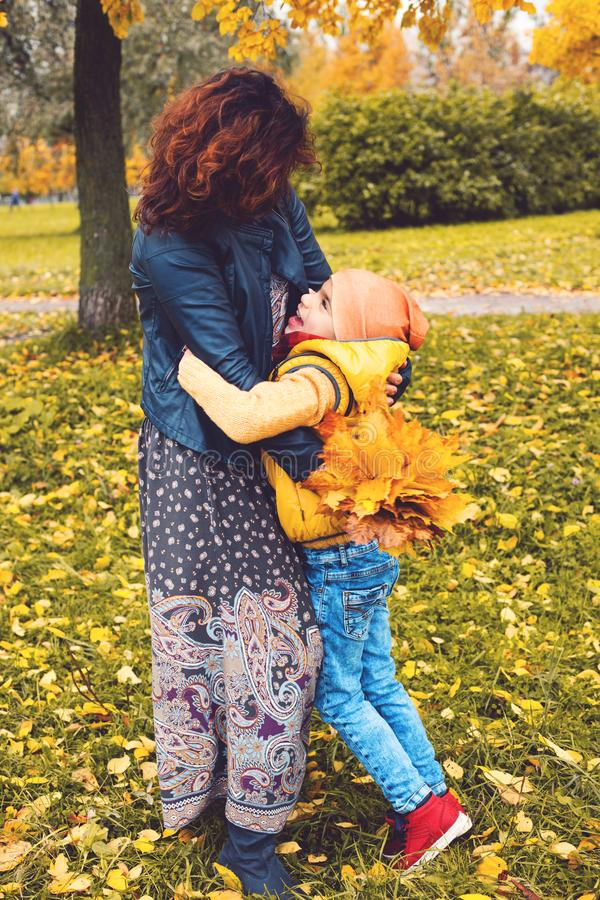 Handsome disabled eight year old boy with his mother in autumn p royalty free stock photo