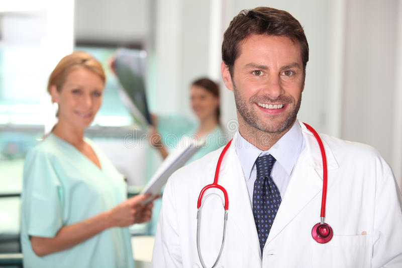 Handsome doctor and colleagues royalty free stock photography