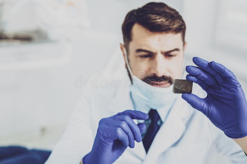 Attentive brunette man examining picture of teeth. Handsome doctor. Competent stomatologist wearing uniform while working in modern clinic royalty free stock images