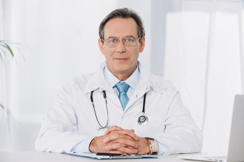 Handsome doctor in glasses sitting at working table and looking. At camera royalty free stock images