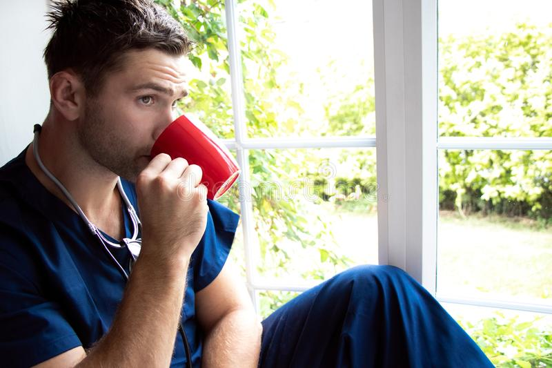 Handsome doctor or male nurse on break looking out of window royalty free stock images