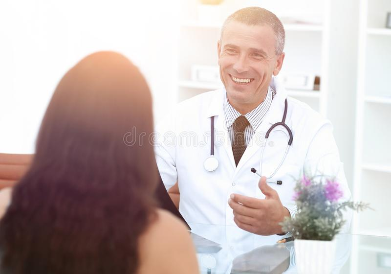 Handsome doctor talking with his patient stock photo