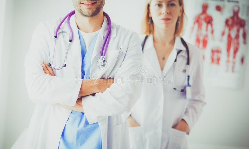 Handsome doctor is talking with young female patient and making notes while sitting in his office stock photography