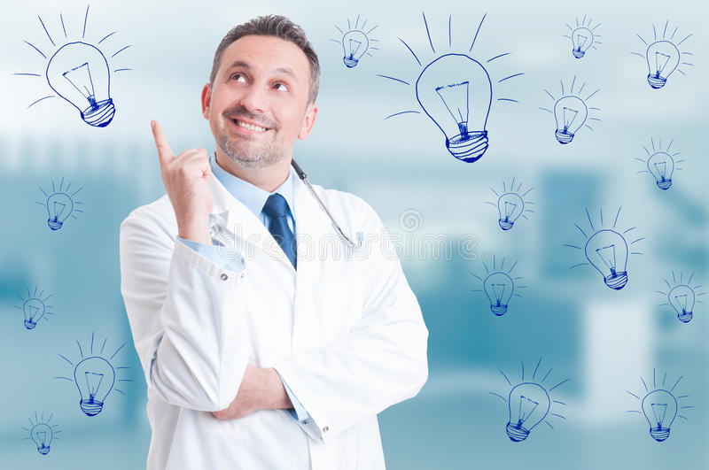Handsome doctor thinking and having a new idea. And smiling joyful on blue background with drawn light bulbs royalty free stock photos