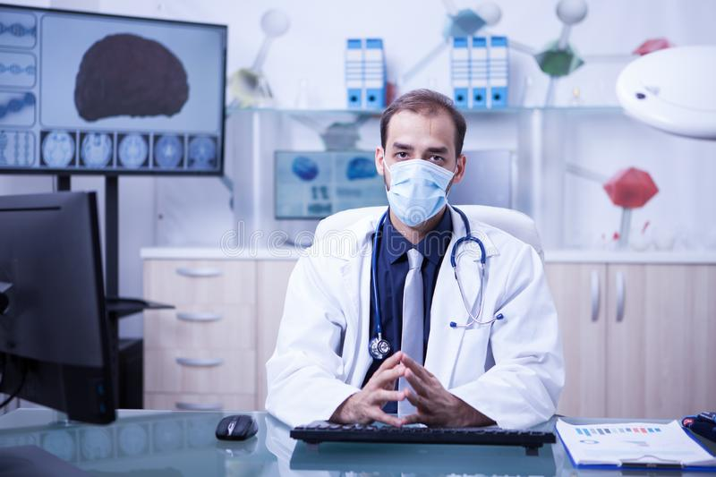 Handsome doctor wearking a mask against germs in the cabinet clinic. Medic following clinic protocol royalty free stock images