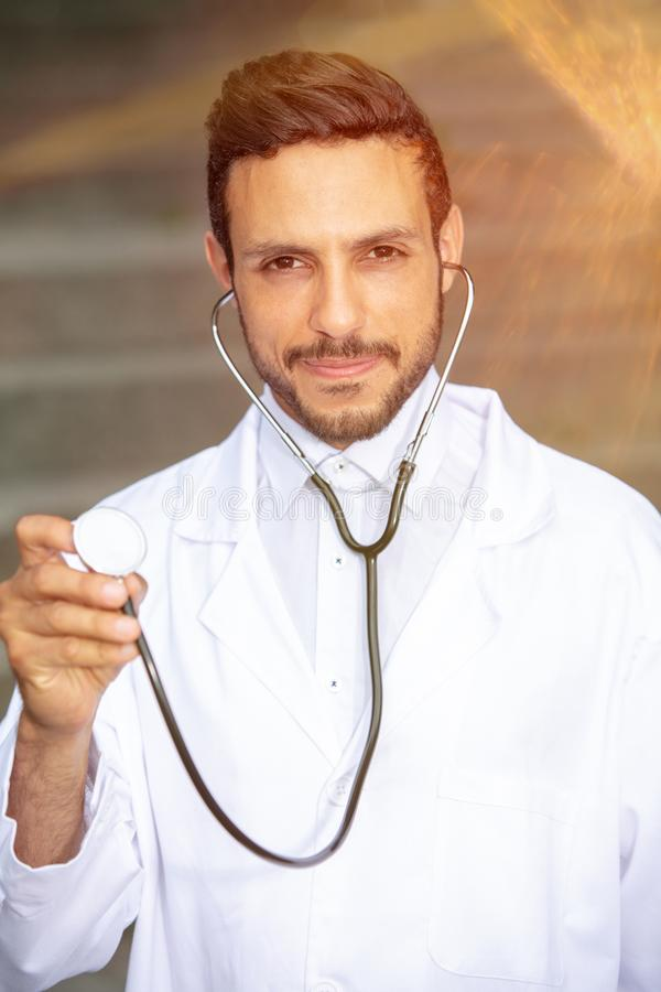 Handsome doctor in white coat with stethoscope stock photos