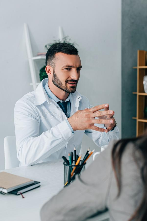Handsome doctor in white coat talking to patient. In clinic royalty free stock photography